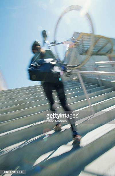 Woman carrying bicycle up stairway, rear view (blurred motion)