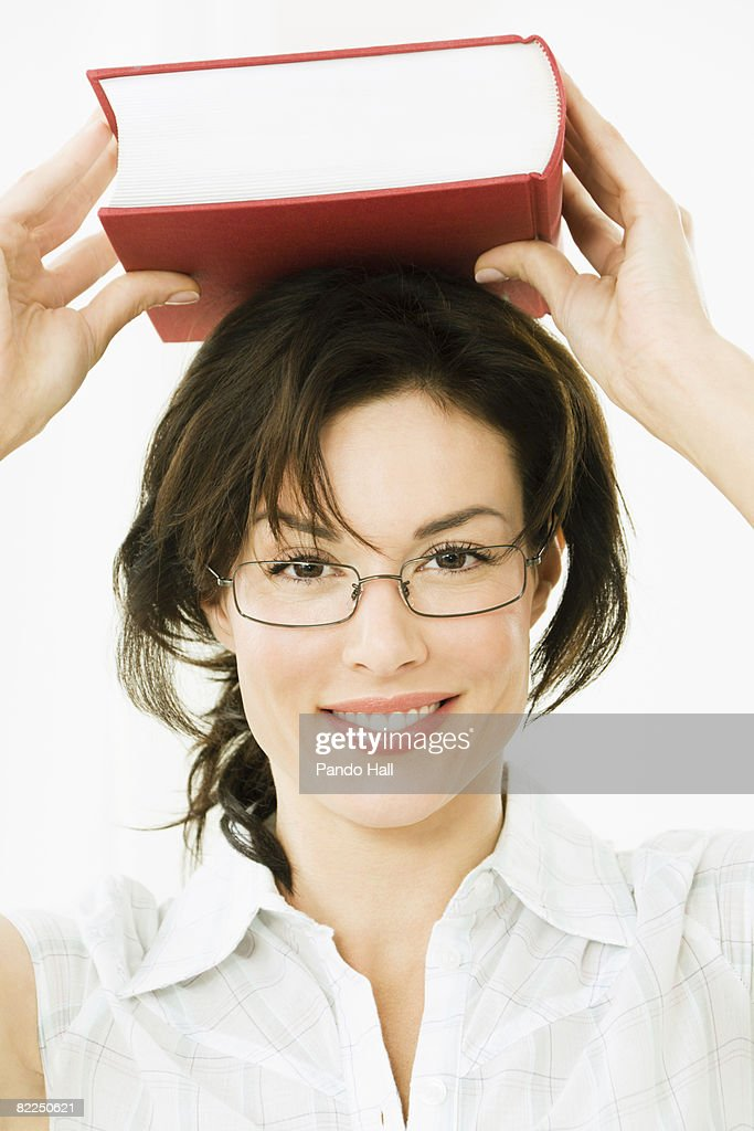 Woman carrying book on head, smiling, portrait : Stock Photo