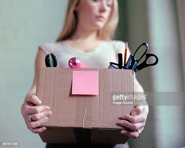 woman carrying box of stationery - downsizing unemployment stock pictures, royalty-free photos & images