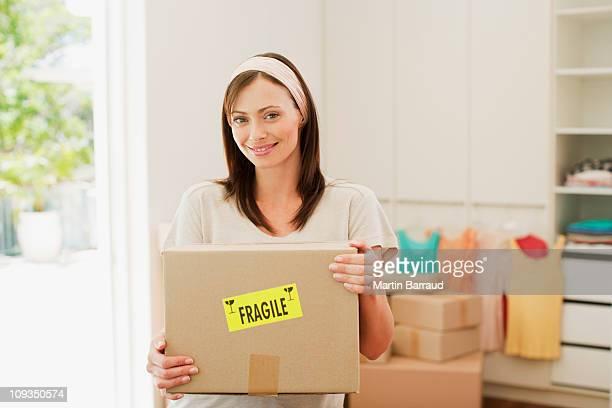 Mulher de caixa de transporte com frágil autocolante na nova casa
