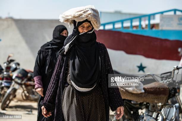 Woman, carrying bread on her head, crosses a main road in Syria's northeastern city of Qamishli on March 9, 2021. - Syria's decade-long war has seen...