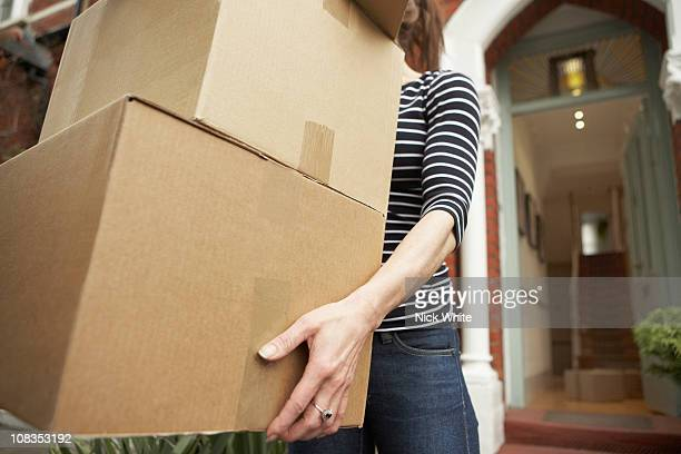 woman carrying brown boxes from house - man made stock pictures, royalty-free photos & images