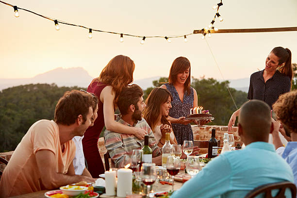 woman carrying cake by friends at table - best friend birthday cake stock pictures, royalty-free photos & images