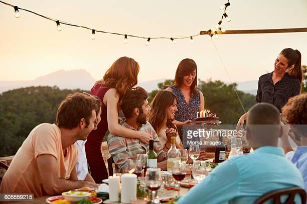 Woman carrying cake by friends at table