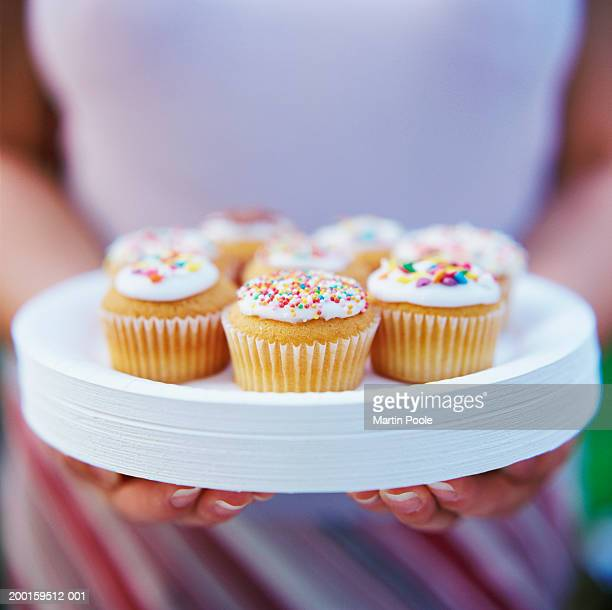 woman carrying cakes on pile of paper plates, mid section, close-up - paper plate stock photos and pictures