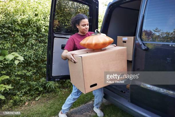woman carrying cardboard box during relocation - einzelne frau über 30 stock-fotos und bilder