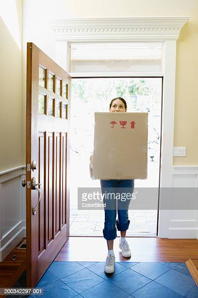 Woman carrying carton into new home