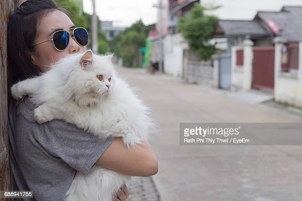 Woman Carrying Cat Leaning By Road In City
