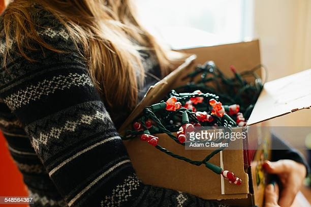 woman carrying christmas lights in cardboard box - christmas decoration stock pictures, royalty-free photos & images