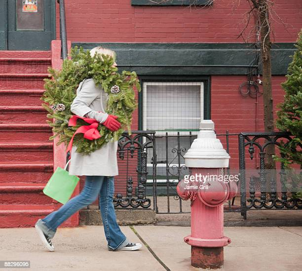 Woman carrying Christmas wreath on urban street