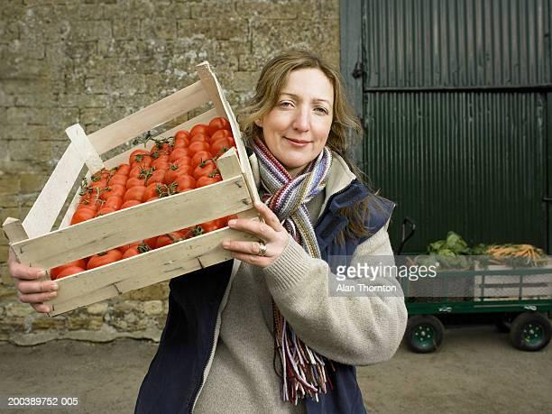 woman carrying crate of tomatoes on shoulder in farmyard, portrait - maduro fotografías e imágenes de stock