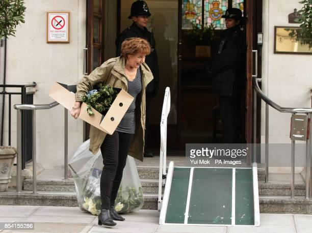 A woman carrying dead flowers leaves the King Edward VII Hospital in London where Queen Elizabeth II is continuing her recovery after being admitted...