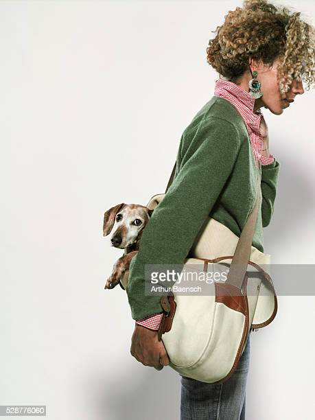 Woman carrying dog in bag