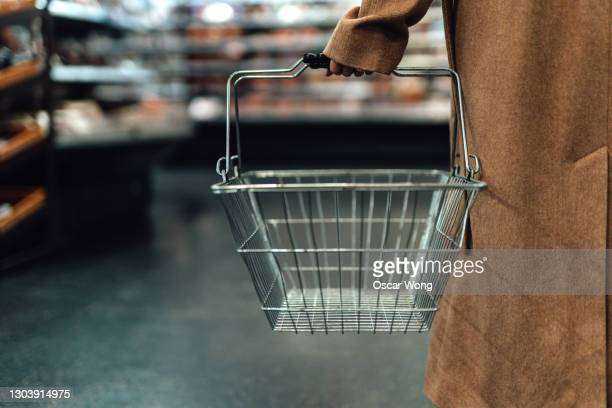 woman carrying empty shopping basket in supermarket - supermarket stock pictures, royalty-free photos & images