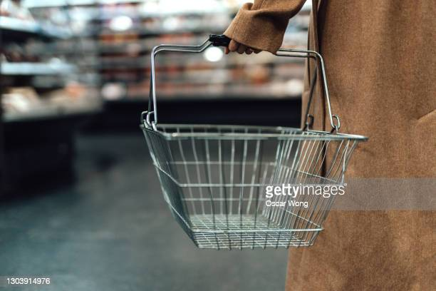 woman carrying empty shopping basket in supermarket - customer stock pictures, royalty-free photos & images