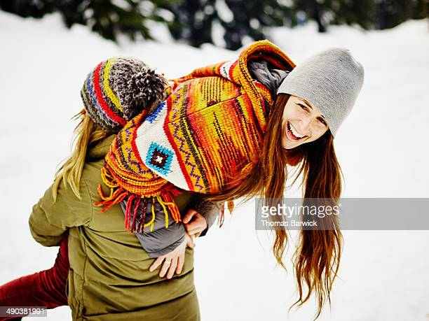 Woman carrying female friend over shoulder