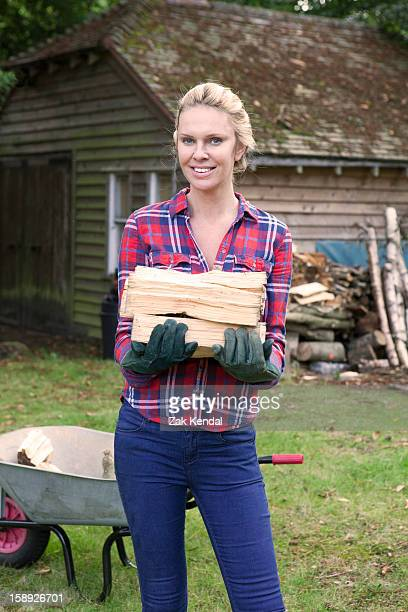 woman carrying firewood in backyard - firewood stock pictures, royalty-free photos & images