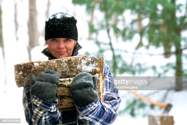 Femme transportant du bois de chauffage.