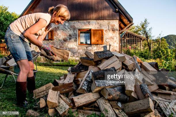 woman carrying firewood with wheelbarrow - firewood stock pictures, royalty-free photos & images