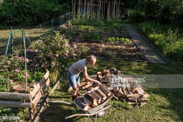 Femme transportant des bois de chauffage avec brouette
