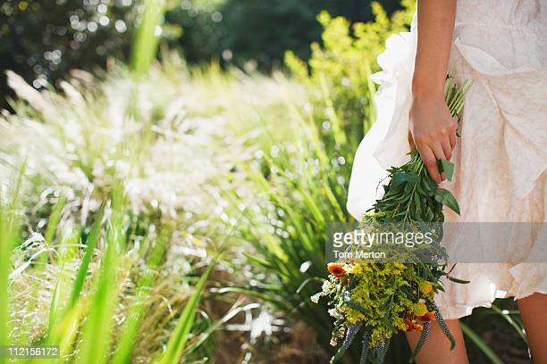 Woman carrying flowers in garden