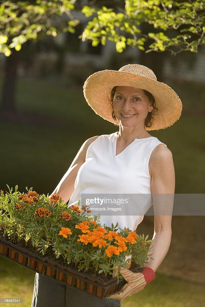 Woman carrying flowers in garden : Stockfoto