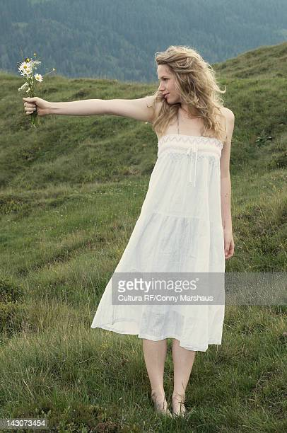 Woman carrying flowers in rural meadow