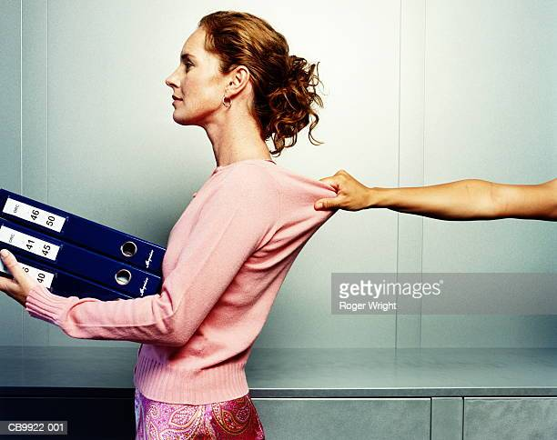 Woman carrying folders, hand grabbing woman's jumper, profile
