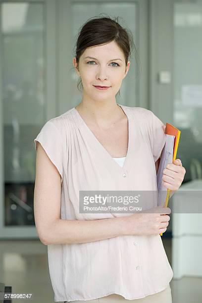 Woman carrying folders, smiling, portrait