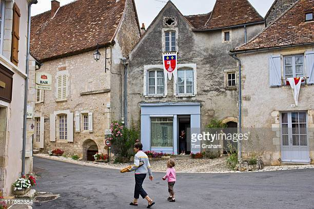 Woman carrying French baguette bread stick walks with child at Angles Sur L'Anglin Vienne PoitouCharantes France