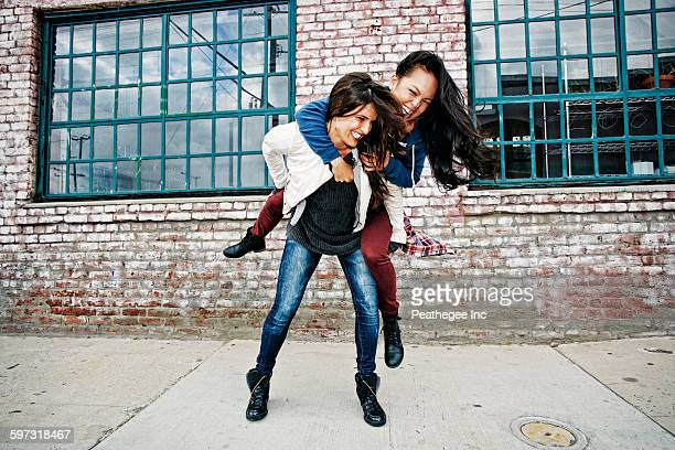 woman carrying friend piggyback - piggyback stock pictures, royalty-free photos & images