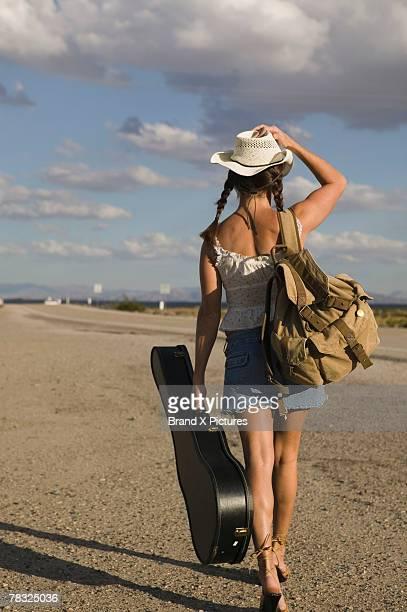 Woman carrying guitar while walking way