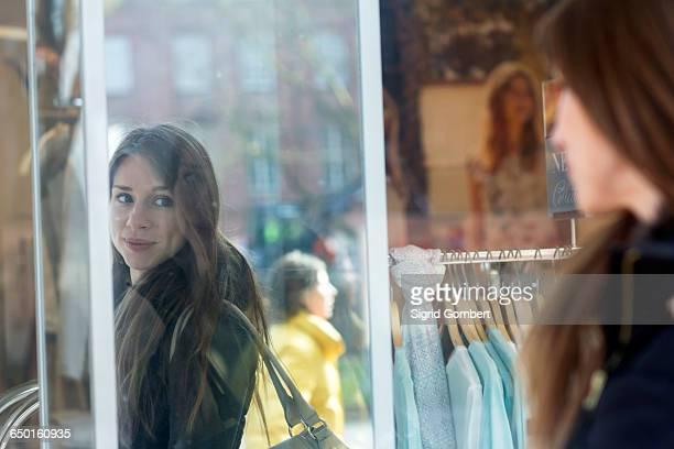 woman carrying handbag looking into shop mirror smiling - sigrid gombert stock-fotos und bilder