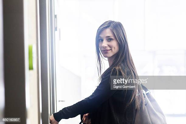 Woman carrying handbag looking over shoulder at camera smiling