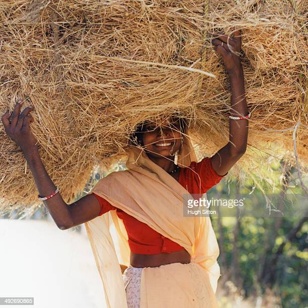 woman carrying hay on her head - hugh sitton stock-fotos und bilder