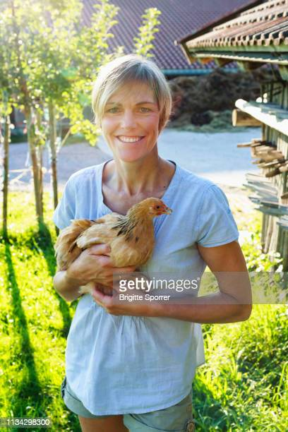 woman carrying hen in countryside, sonthofen, bayern, germany - bayern stock pictures, royalty-free photos & images