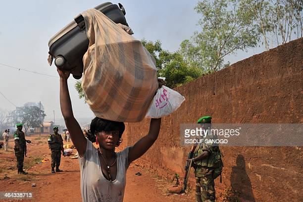 A woman carrying her belongings on her head walks past Rwandan soldiers from the MISCA as she flees her neighborhood following an attack by...