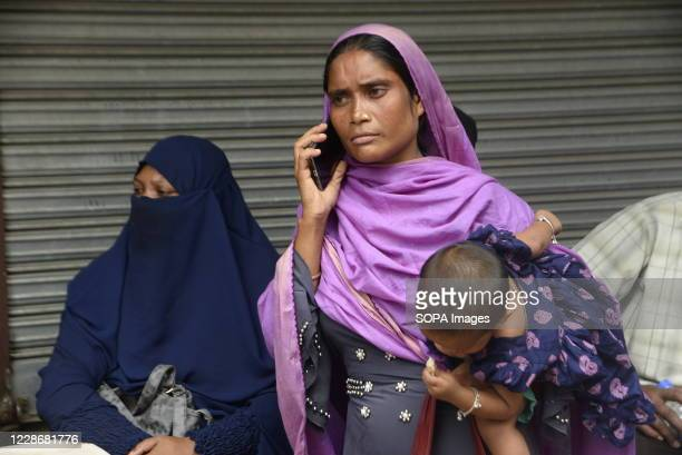 Woman carrying her child is seen on a phone in front of Biman Bangladesh Airlines office as she waits for her air ticket to return back to her...