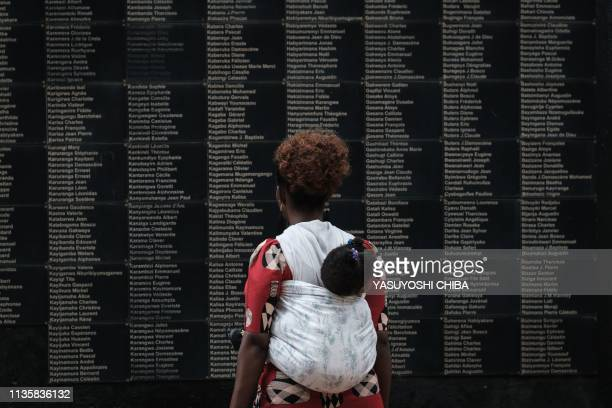 TOPSHOT A woman carrying her child looks at the wall of victims' names as Rwanda marks the 25th Commemoration of the 1994 Genocide at the Kigali...