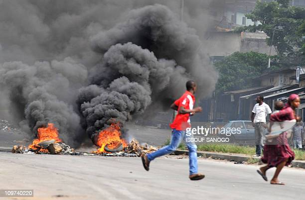 A woman carrying her child runs past supporters of Alassane Dramane Ouattara burning tyres on a street of Abidjan on February 24 2011 The government...
