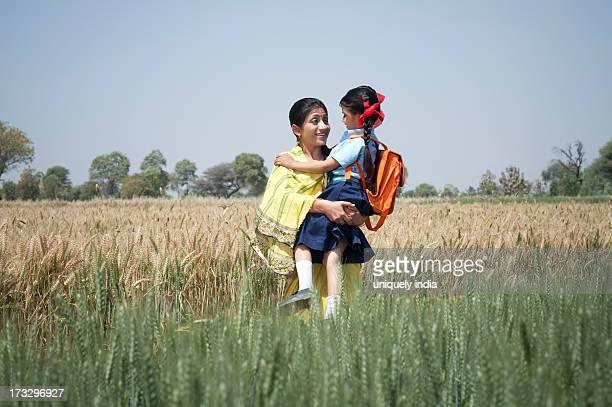 Woman carrying her schoolgirl in the field, Sohna, Haryana, India