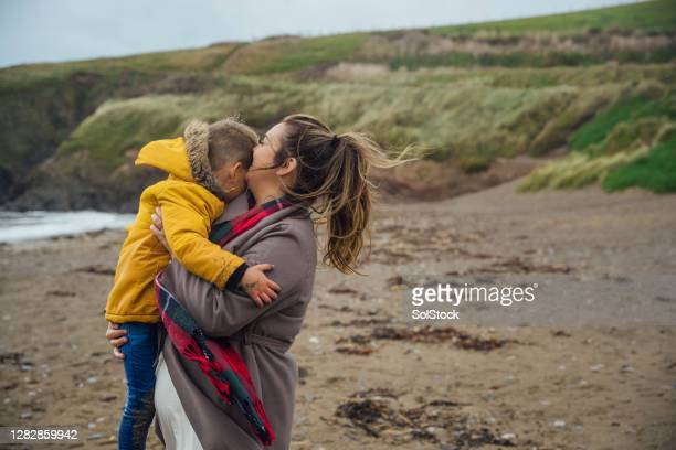 woman carrying her son on the beach - primary age child stock pictures, royalty-free photos & images