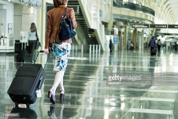A woman carrying her suitcase in an airport