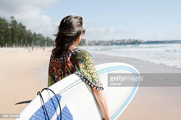 Woman Carrying Her Surfbard On The Beach