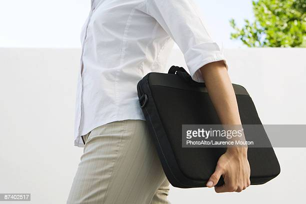 Woman carrying laptop bag, cropped view of mid section
