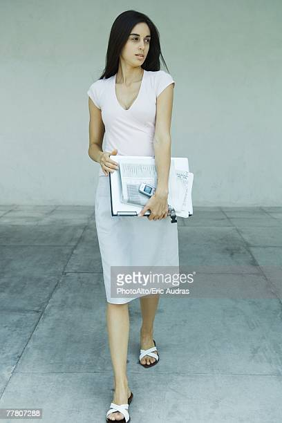 Woman carrying laptop, newspaper and cell phone under arm, full length portrait