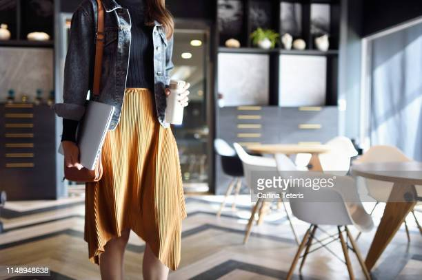 woman carrying laptop, purse and reusable coffee cup to work - green skirt stock pictures, royalty-free photos & images