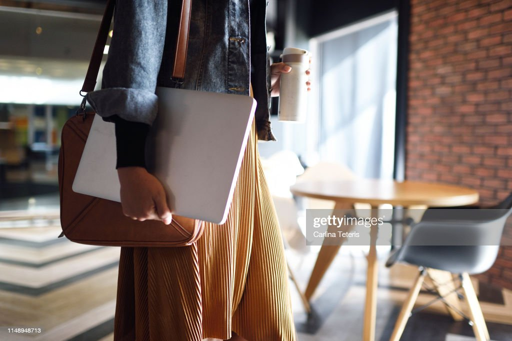 Woman carrying laptop, purse and reusable coffee cup to work : Stock Photo