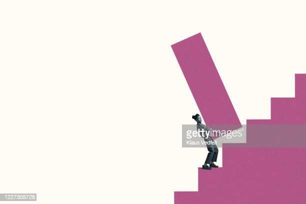 woman carrying large magenta bar graph on steps - バイアス ストックフォトと画像