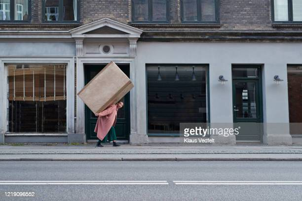 woman carrying large package on footpath in city - over burdened stock pictures, royalty-free photos & images